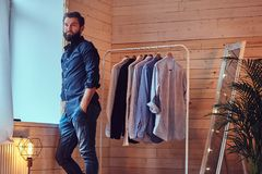 A man fit on fashionable shirts. Attractive bearded tattooed male fit on fashionable shirts in a store changing room Stock Photos
