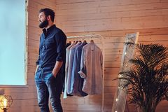 A man fit on fashionable shirts. Attractive bearded tattooed male fit on fashionable shirts in a store changing room Royalty Free Stock Photo
