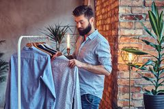 A man fit on fashionable shirts. Attractive bearded tattooed male fit on fashionable shirts in a store changing room Royalty Free Stock Image
