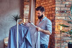 A man fit on fashionable shirts. Attractive bearded tattooed male fit on fashionable shirts in a store changing room Royalty Free Stock Photography