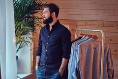A man fit on fashionable shirts. Attractive bearded tattooed male fit on fashionable shirts in a store changing room Royalty Free Stock Photos