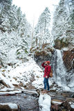 Attractive bearded young man walking near mountain waterfall in winter. Attractive bearded young man in checkered shirt and jeans walking near mountain waterfall Stock Images