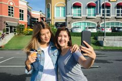 Attractive beautiful asian friends women using a smartphone. Happy young asian teenage at urban city while taking self portraits. Royalty Free Stock Image