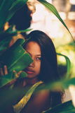 Attractive beautiful Asian girl hiding behind the leaf Stock Image
