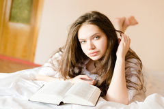 Attractive beautiful brunette young woman student girl with book looking at camera. Closeup on brunette young woman with book looking at camera relaxing in bed Stock Photo