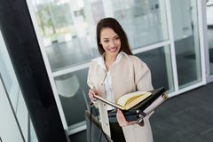 Attractive and beautiful businesswoman holding files in hands Stock Images