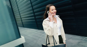 Attractive and beautiful businesswoman walking while taking call Stock Photos