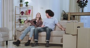 Attractive beautiful couple enjoying the time while they moving in a new house after a hard carrying day they take a sit. On the sofa and watching tv stock footage