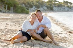Attractive beautiful  couple in love sitting on the beach in romantic summer holidays Royalty Free Stock Photography