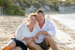 Attractive beautiful  couple in love sitting on the beach in romantic summer holidays Royalty Free Stock Images