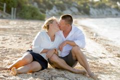 Attractive beautiful  couple in love sitting on the beach in romantic summer holidays Royalty Free Stock Image