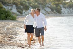 Attractive beautiful  couple in love walking on the beach kissing in romantic summer holidays Stock Photography