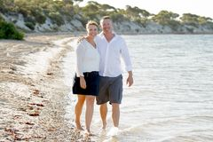 Attractive beautiful  couple in love walking on the beach in romantic summer holidays Royalty Free Stock Photo