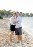 Attractive beautiful couple in love walking on the beach in romantic summer holidays. Young attractive and beautiful American couple in love walking on the beach stock photos