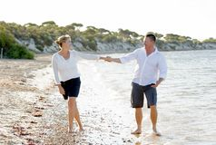 Attractive beautiful  couple in love walking on the beach in romantic summer holidays Royalty Free Stock Image