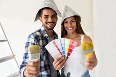 Attractive beautiful couple ready for painting new home. Attractive beautiful smiling couple holding brush ready for painting new home stock image