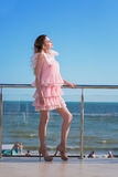 An attractive and beautiful female in a pink dress is posing on a sunny hotel`s balcony. Luxurious lifestyle. royalty free stock image