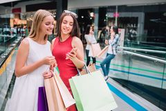 Attractive and beautiful girls are standing together with bags. Brunette girl is holding phone and looking at it. Together with her friend. Blonde girl is stock image