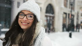 Attractive beautiful lady posing and flirting on camera over snowy city background stock footage