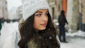 Attractive beautiful lady walking over snowy city background. Attractive beautiful lady holding on camera over snowy city background stock footage