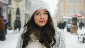 Attractive beautiful lady walking over snowy city background stock video