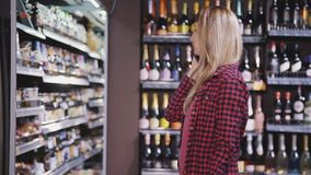 Mature woman choosing bottle of quality alcohol and talking on c. Attractive and beautiful mature woman in casual wear clothes choosing items in supermarket near stock footage