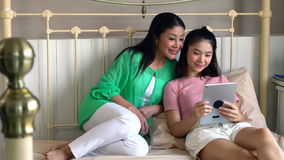 Attractive beautiful mother with daughter using tablet playing g stock images