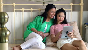 Attractive beautiful mother with daughter using tablet playing game stock video
