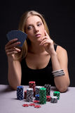 Attractive beautiful serious woman playing poker in casino Stock Images