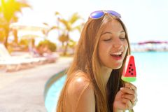 Attractive beautiful smiling woman eating popsicle ice pop in form of watermelon slice. Summer holidays concept stock photo