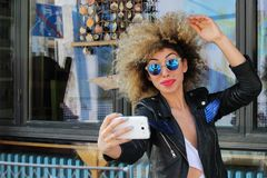 Attractive beautiful stylish young girl take selfie. Spring time sunglassesn Stock Images