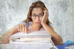 Attractive and beautiful tired student girl leaning on school books pile tired and bored after studying preparing exam looking was stock photo