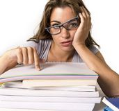 Attractive and beautiful tired student girl leaning on school books pile tired and exhausted after studying preparing exam looking royalty free stock photography