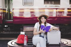 Attractive beautiful tourist woman is reading travel guide book stock image