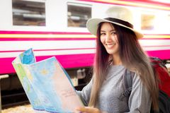 Attractive beautiful traveler woman holding the map and standing at train station. Charming beautiful young woman is planning to stock photo