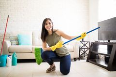 Cute woman playing guitar with broom. Attractive beautiful woman aspiring to become a musician using broom as guitar Royalty Free Stock Photography