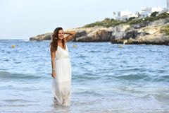 Attractive and beautiful woman enjoying vacation summer holidays at Spain coast village walking on beach Stock Photo