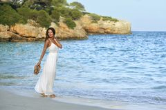 Attractive and beautiful woman enjoying vacation summer holidays at Spain coast village walking on beach Royalty Free Stock Image