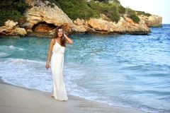 Attractive and beautiful woman enjoying vacation summer holidays at Spain coast village walking on beach. Young attractive and beautiful woman enjoying vacation Royalty Free Stock Photos
