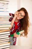 Attractive beautiful woman geek in study with pile of books.  Stock Images