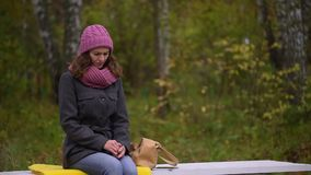 Unhappy beautiful woman having a headache while sitting on bench in autumn park. slow-motion. Attractive beautiful woman having headache, outdoors. slow-motion stock video footage