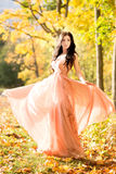 Attractive beautiful woman. Nature, autumn, fall yellow leafs. Fashion orange dress Stock Photo