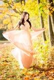Attractive beautiful woman. Nature, autumn, fall yellow leafs. Fashion orange dress Royalty Free Stock Photography