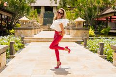 Attractive woman in red leather pants and high heels. Attractive and beautiful woman in red leather pants and red high heels Royalty Free Stock Image
