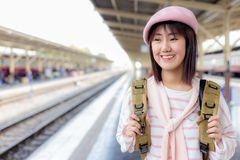 Attractive beautiful woman stand at train station and going to some place by train. Lovely woman love traveling everywhere alone royalty free stock photography