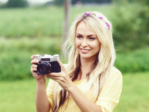 Attractive, beautiful, young girl taking pictures outdoors. Holi. Attractive, young hippie girl taking pictures outdoors at summer. Holiday, vacation, hobby Royalty Free Stock Images