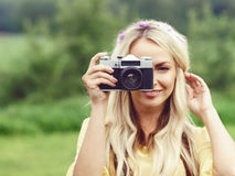 Attractive, beautiful, young girl taking pictures outdoors. Holi. Attractive, young hippie girl taking pictures outdoors at summer. Holiday, vacation, hobby Stock Photos