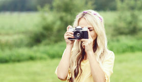 Attractive, young hippie girl taking pictures outdoors at summer. Holiday, vacation, hobby concept. royalty free stock photography