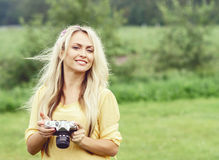 Attractive, young hippie girl taking pictures outdoors at summer. Holiday, vacation, hobby concept. stock photography