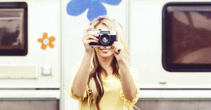 Attractive, young hippie girl taking pictures outdoors at summer. Holiday, vacation, hobby concept. stock photo